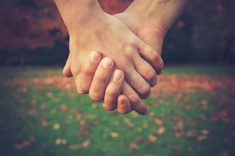 Couple holding hands in park stock photos