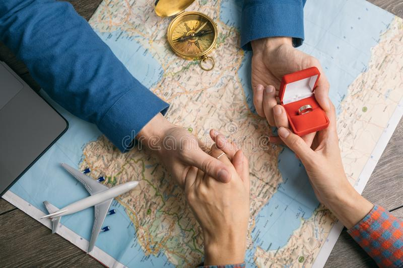 Couple holding hands. Proposing. Travel planning. Top view table with map. Romantic moment stock photography