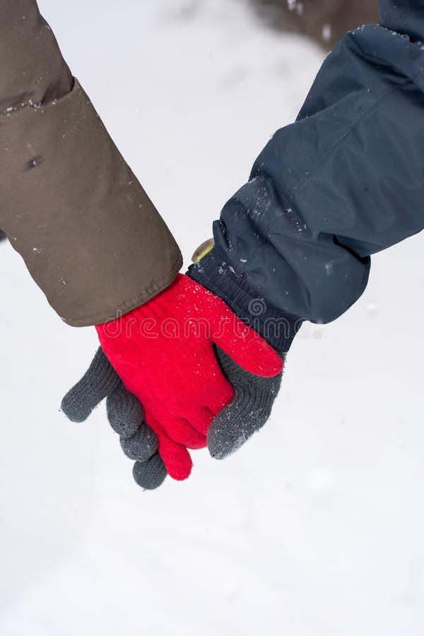Couple holding hands in snow covered park stock photography