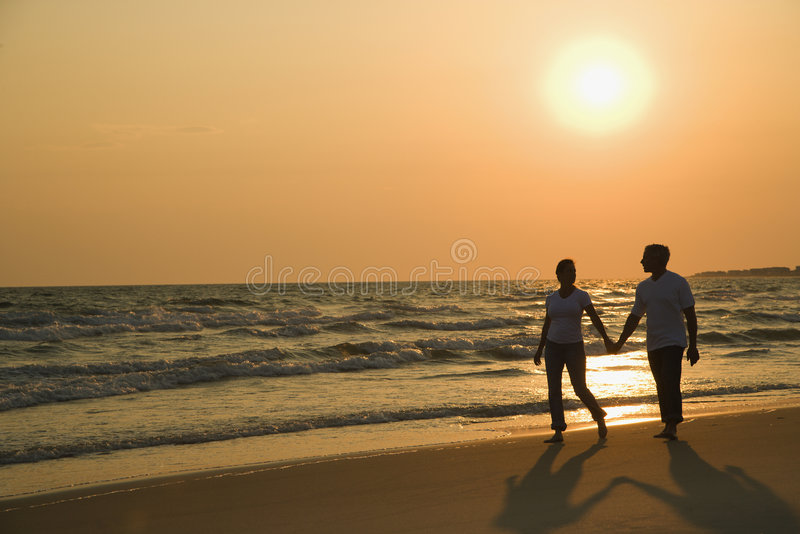 Couple holding hands at sunset. Caucasian mid-adult couple holding hands and walking down beach at sunset royalty free stock photo