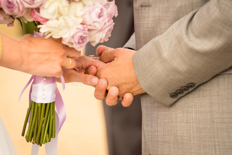 A couple holding hands during their wedding ceremony royalty free stock image