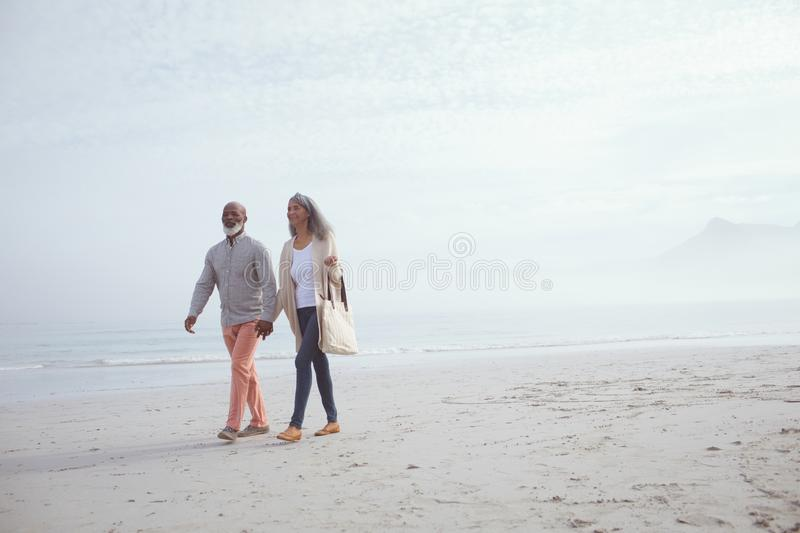Couple holding hands while walking by the beach royalty free stock photo