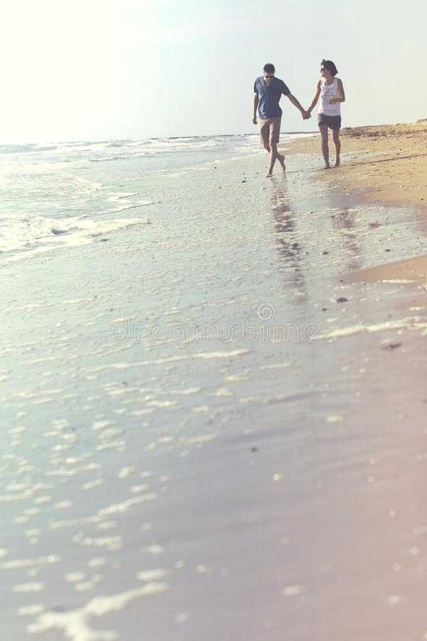 Couple holding hands walking on the beach. In harmony with themselves and nature stock photo