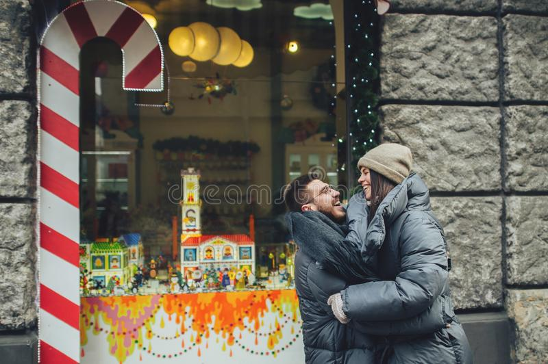 Happy couples on the city square decorated for a Christmas marke stock image