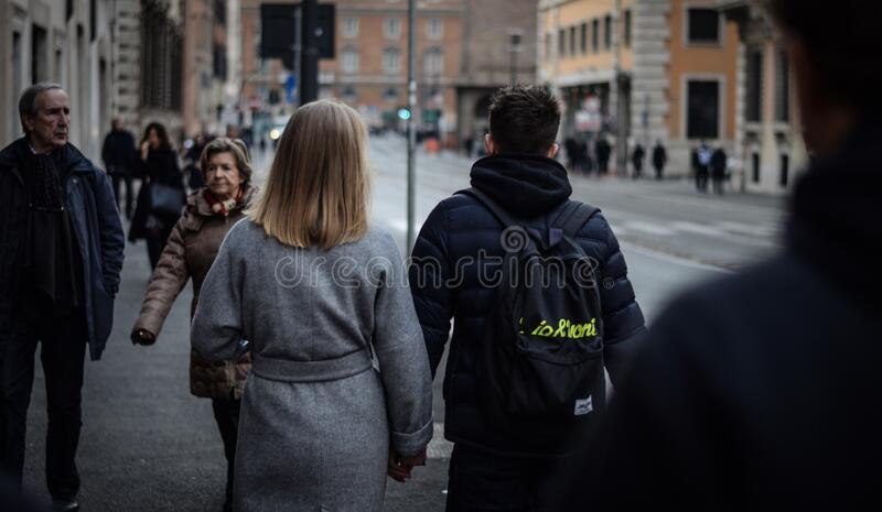 Couple Holding Hands While Walking on the Street royalty free stock photo