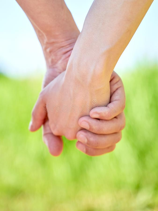 Couple holding hands and walking in sunny summer weather stock image