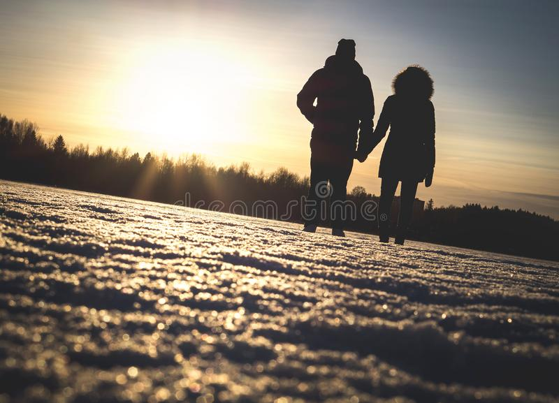 Couple holding hands in winter sunset. stock photos