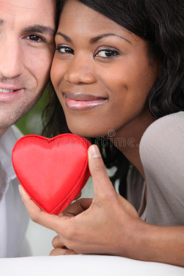 Couple holding a heart case. Loving couple holding a heart case stock photography