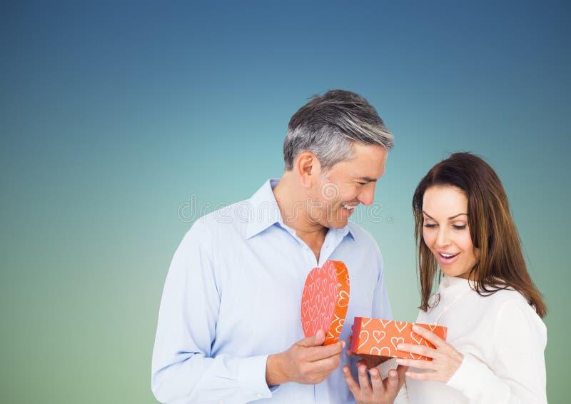 Couple holding heart shaped gift box. Against blue background royalty free stock photo