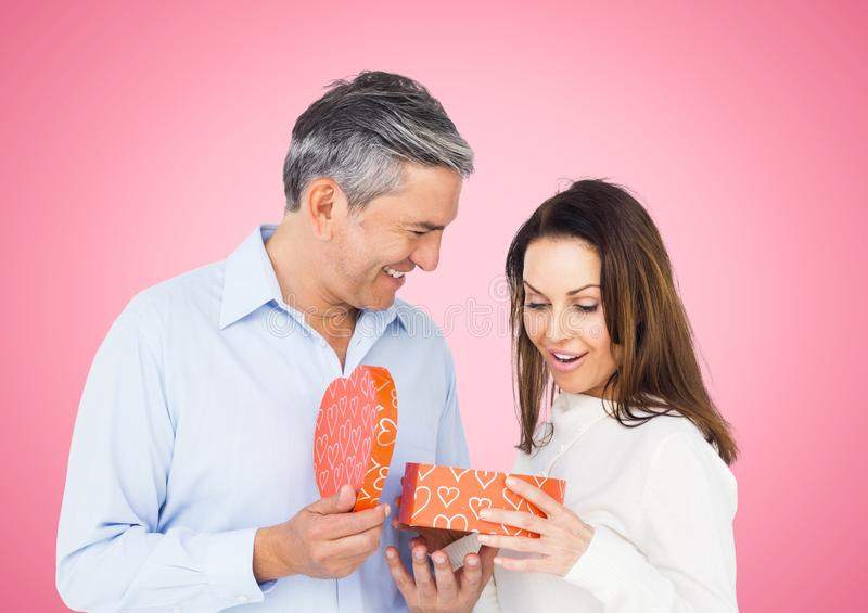 Couple holding heart shaped gift box. Against pink background royalty free stock photos
