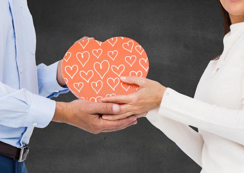 Couple holding heart shaped gift box. Mid section of couple holding heart shaped gift box against black background stock images
