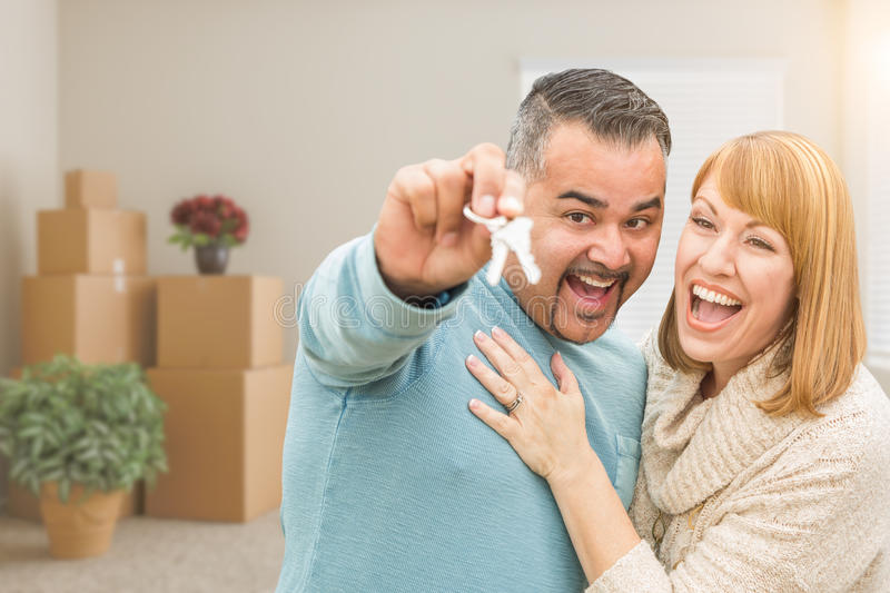 Couple Holding House Keys Inside Empty Room with Moving Boxes. Mixed Race Couple Holding House Keys Inside Empty Room with Moving Boxes royalty free stock photo