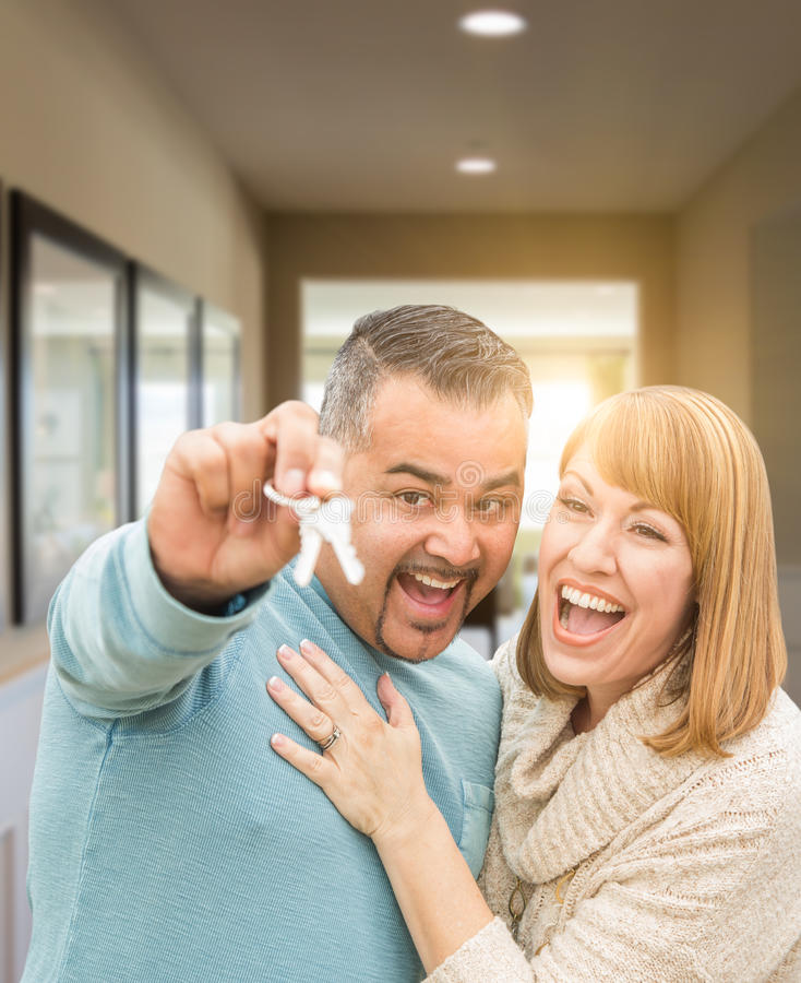 Couple Holding House Keys Inside Hallway of Their New Home. Mixed Race Couple Holding House Keys Inside Hallway of Their New Home stock photo