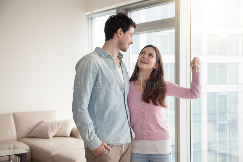 Couple holding new apartment keys, real estate and family concep. Young smiling couple holding and showing keys of their new own home, happy family buying or royalty free stock photography
