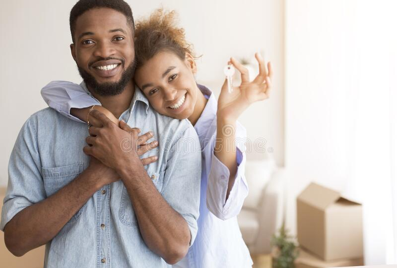 Couple Holding New Home Key Hugging Standing In Own House stock image