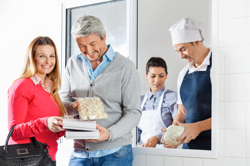 Couple Holding Pasta Packets By Chefs At Window stock photo