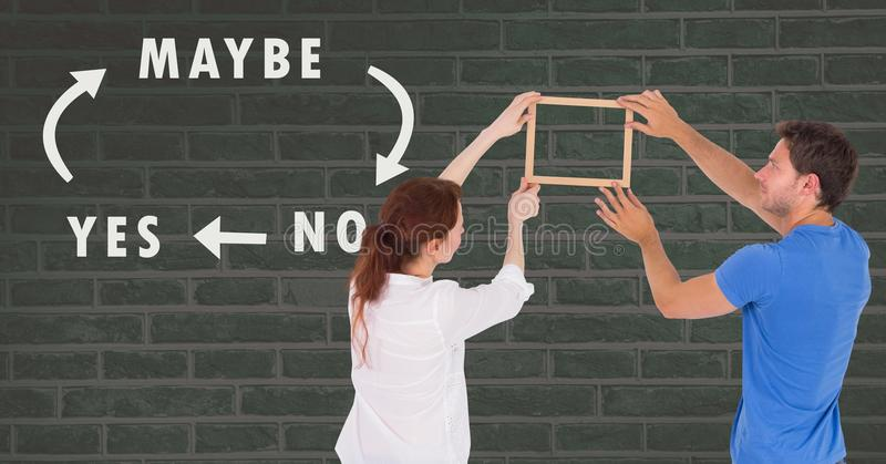 Couple holding picture frame against wall with Yes No Maybe text and arrows stock photos
