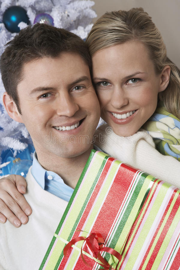 Couple Holding Present By Christmas Tree royalty free stock photos