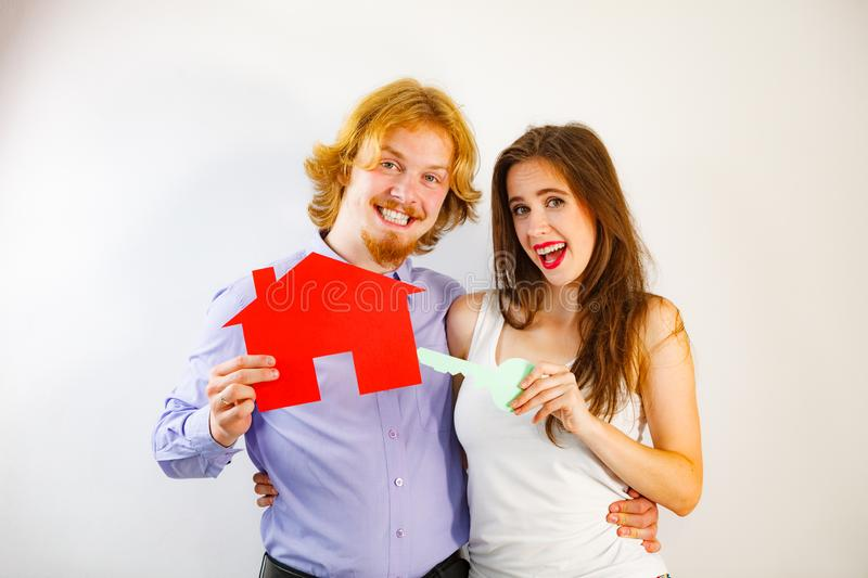 Couple holding real estate paper symbols. Smiling young couple holding paper house with key. Husband and wife dreaming about new home. Housing. real estate royalty free stock photography
