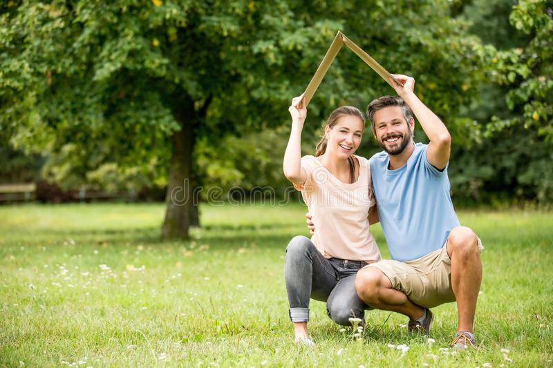 Couple holding roof as home concept stock photos