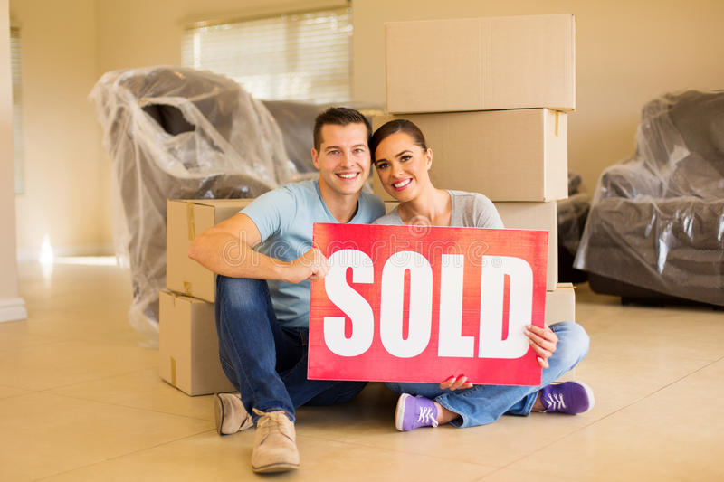 Couple holding sold sign stock photo