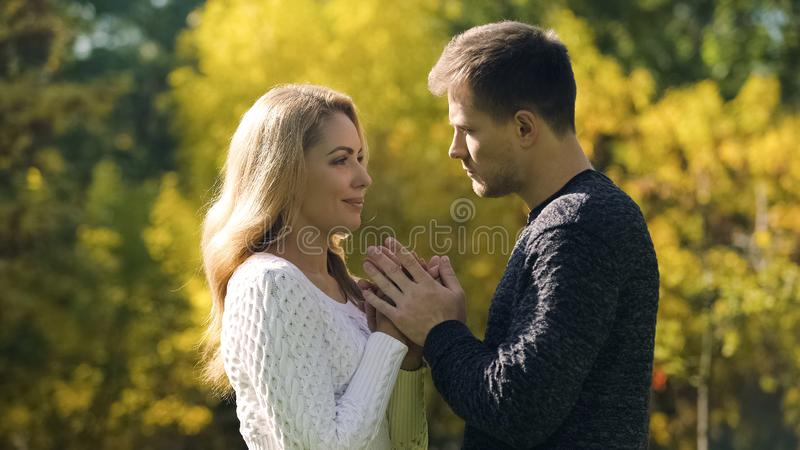 Couple holding and warming hands in cold autumn day, taking care of beloved royalty free stock photography