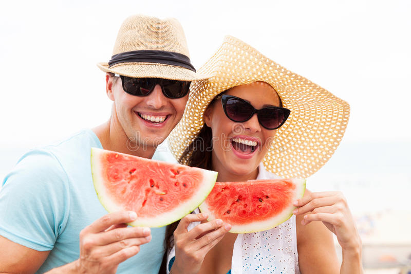 Couple holding watermelon. Cheerful couple holding slices of watermelon stock image
