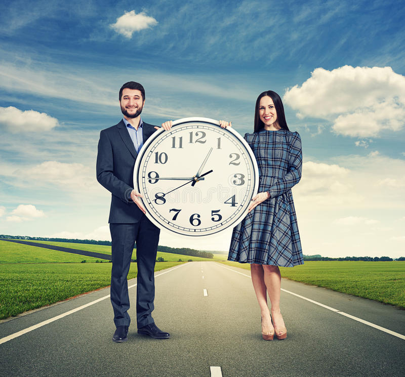 Couple holding white clock. Smiley couple holding white clock and looking at camera. photo at outdoor stock photos