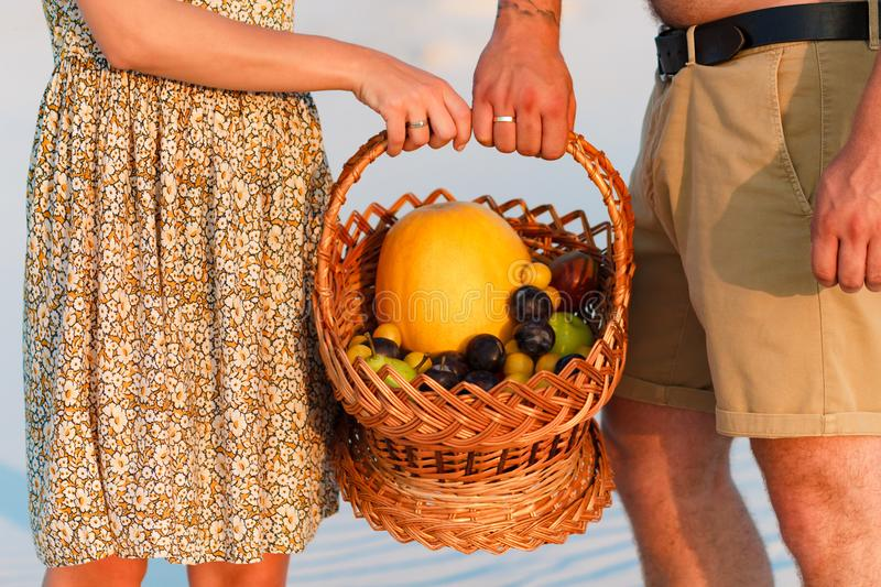 Couple holding a wicker basket with fruit, man and woman having a picnic on the white sand beach or in the desert or in the sand d stock photo