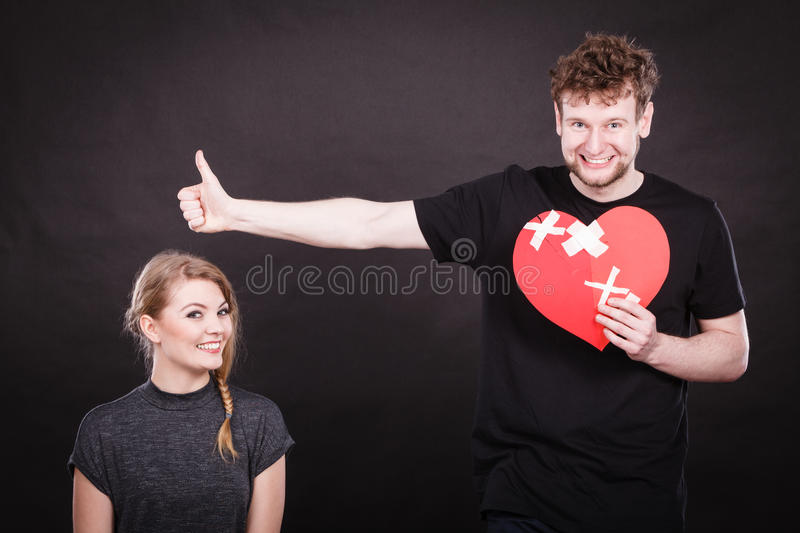 Couple holds broken heart joined in one. Heal love concept. Couple women and men holding two halves of broken heart fixed with plaster bandage going to be joined stock image