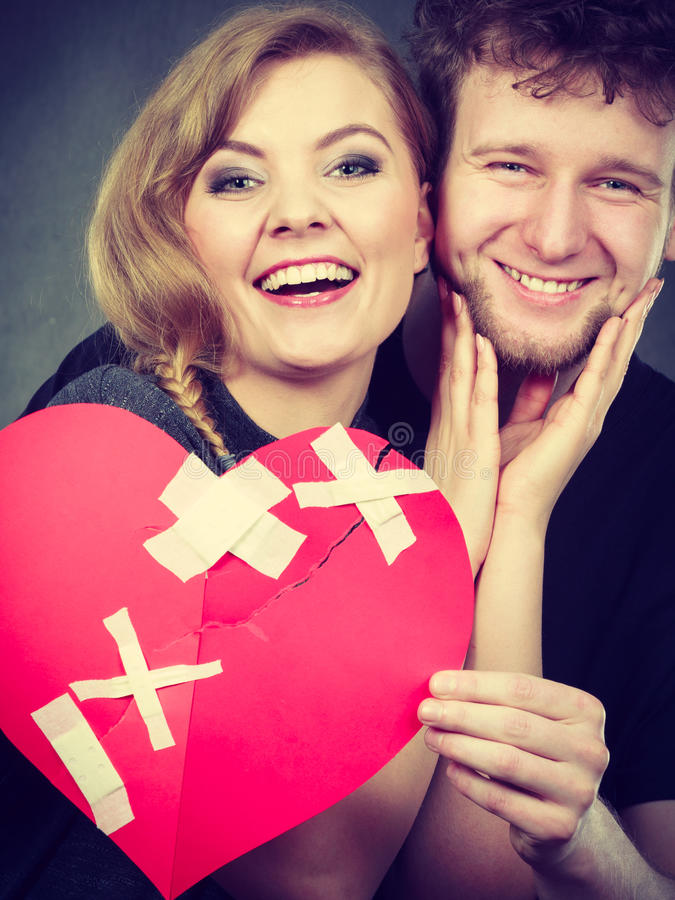 Couple holds broken heart joined in one. Heal love concept. Couple women and men holding two halves of broken heart fixed with plaster bandage going to be joined royalty free stock photos