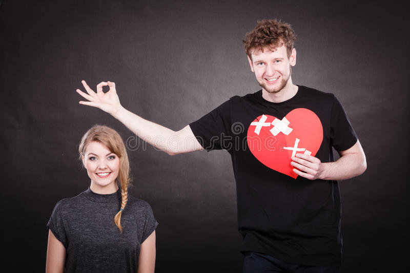 Couple holds broken heart joined in one. Heal love concept. Couple women and men holding two halves of broken heart fixed with plaster bandage going to be joined royalty free stock image