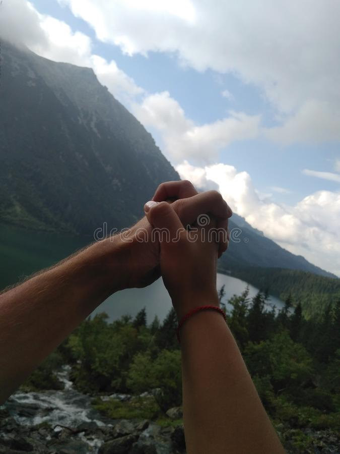 Couple holds hands together on the background. A loving couple holds hands on the background of nature and mountains. Hands in lock up royalty free stock photos