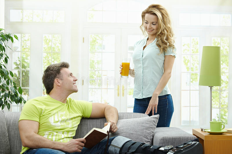 Couple at home. Man rasting his broken leg in cast on sofa at home, reading book. Woman bringing him orange juice stock photo