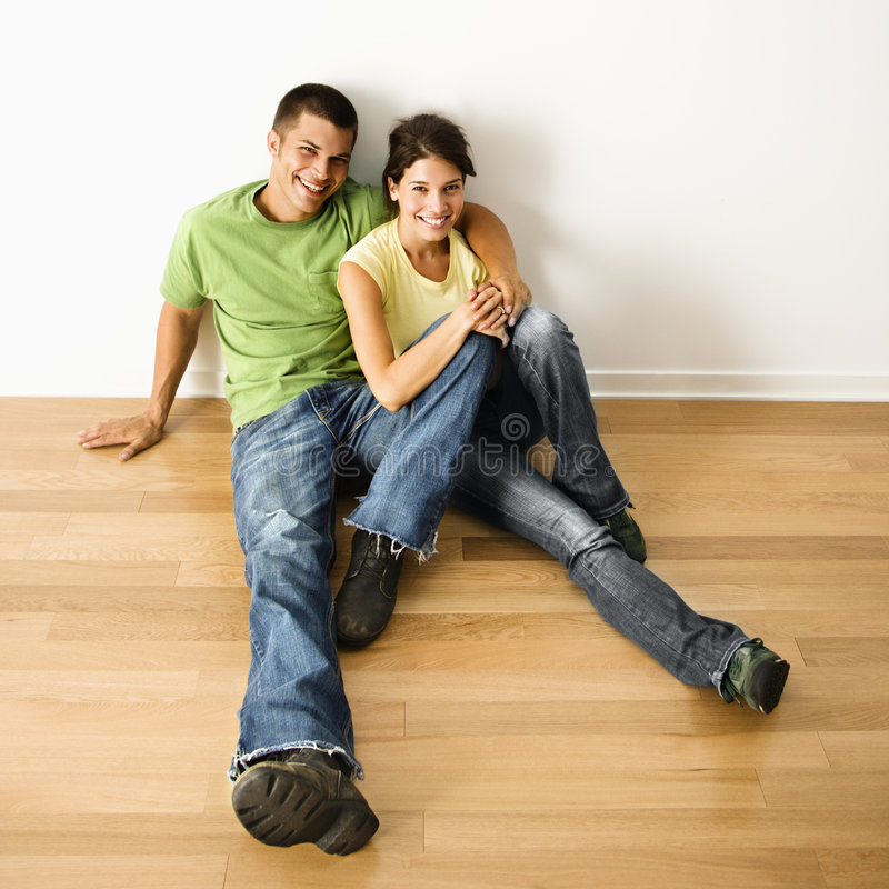 Couple in home. Attractive young adult couple sitting close on hardwood floor in home smiling royalty free stock photo
