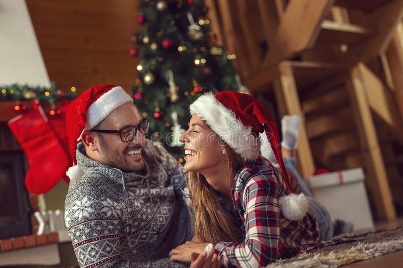 Couple at home on a Christmas morning. Beautiful young couple in love wearing santa hats, ing on the floor next to a fireplace and a nice decorated Christmas stock photography