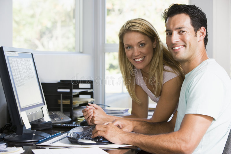Couple in home office with computer smiling royalty free stock images