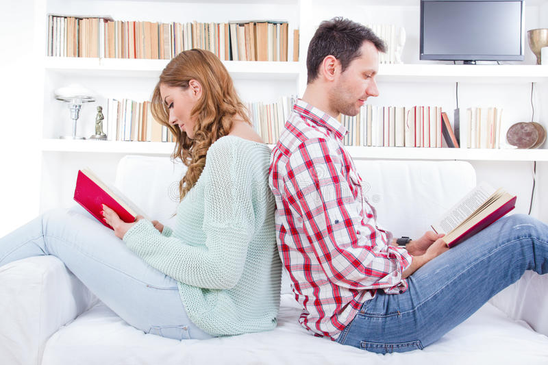 Couple at home reading book. Couple at home. Cheerful young men sitting and reading book while his girlfriend or women sitting behind him leaning back to back stock images
