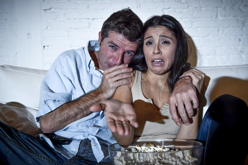Couple at home sofa couch hug watching television movie together looking sad crying depressed. Young couple at home sofa couch hug watching television movie royalty free stock images