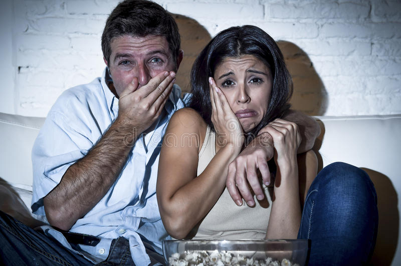 Couple at home sofa couch hug watching television movie together. Young couple at home sofa couch hug watching television movie together looking sad crying stock photo