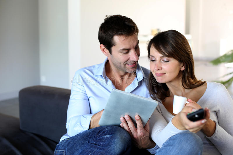 Couple at home using tablet stock image