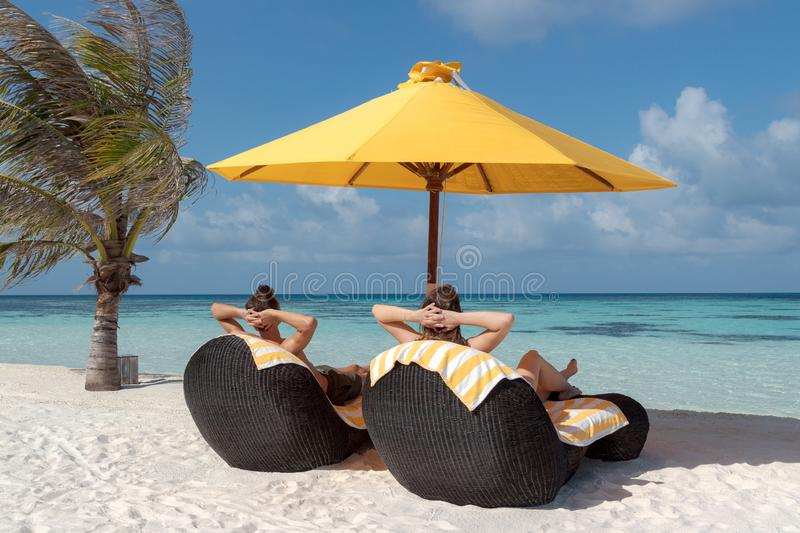 Couple in honeymoon lying on sun chairs in the Maldives. Crystal clear blue water as background. Holiday in paradise concept. Freedom and happiness concept royalty free stock photos