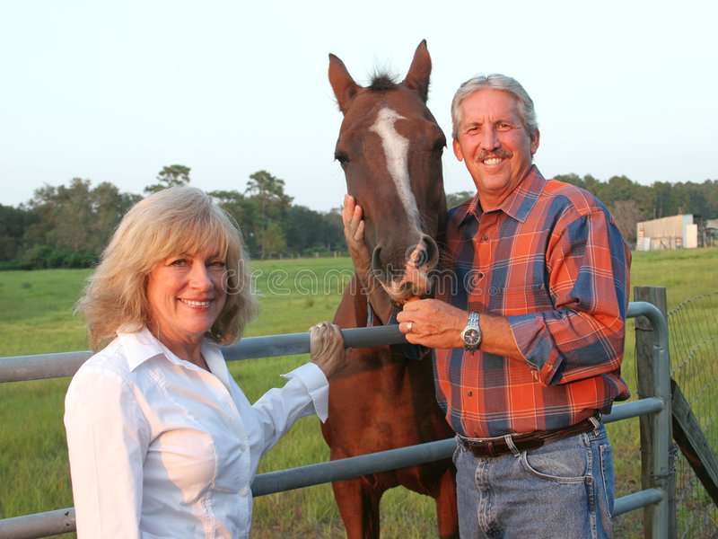 Couple With Horse. A handsome farm couple posing with their favorite horse