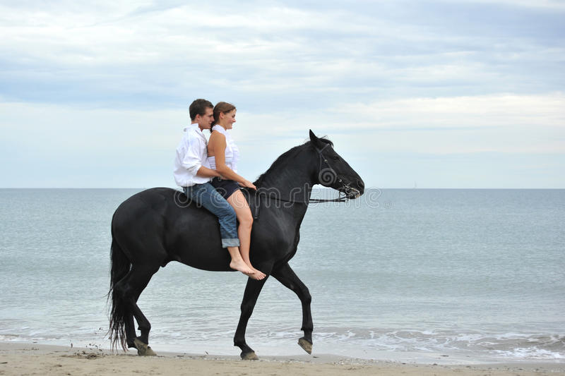 Couple and horse on the beach royalty free stock photography