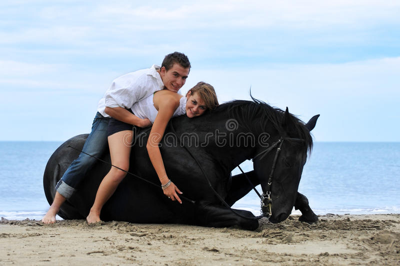 Couple and horse on the beach royalty free stock photos