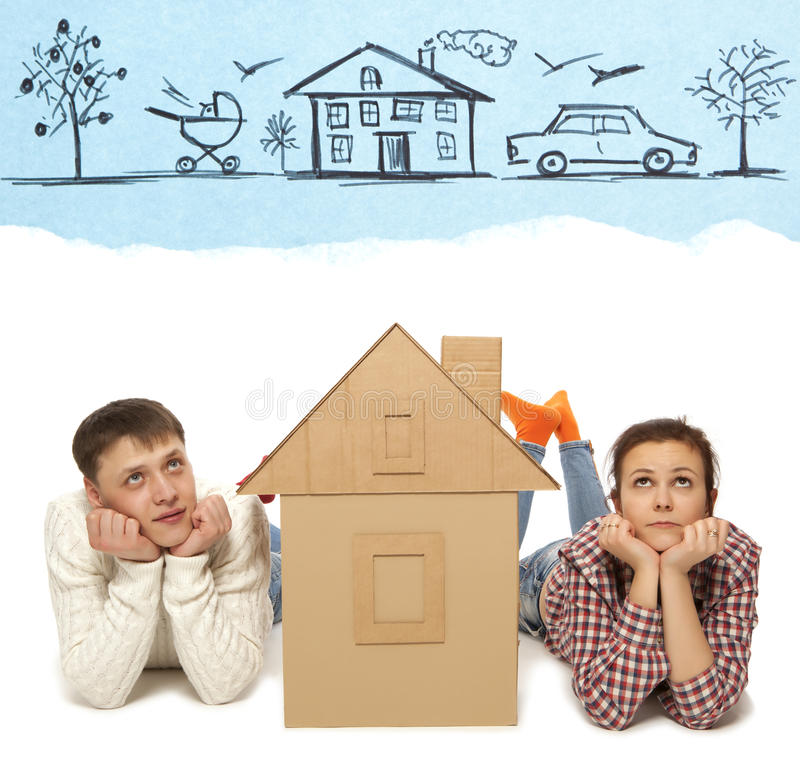 Couple with house of cardboard. Young couple with the house of cardboard. Photo and hand-drawing elements combined stock photos