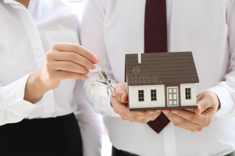 Couple with house model and key, closeup. Mortgage concept royalty free stock photo