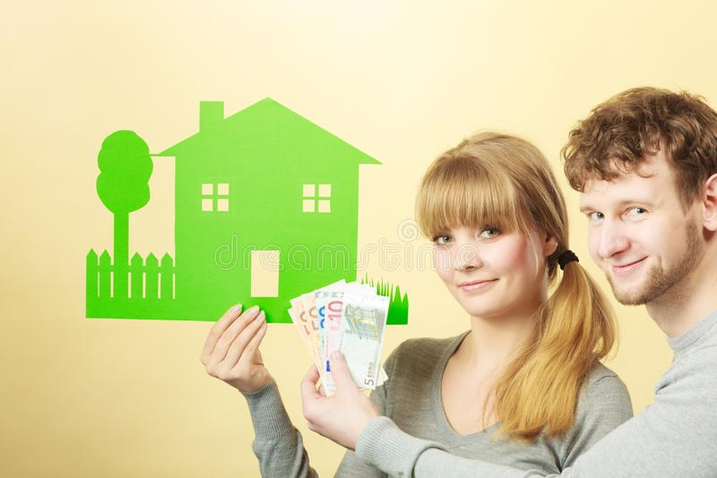 Couple with house and money. Home real estate credit mortgage concept. Couple with house and money. Young man and woman counting banknotes and holding cartboard stock image