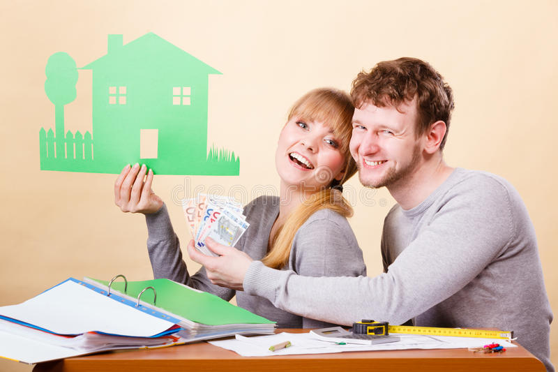 Couple with house and money. Home real estate credit mortgage concept. Couple with house and money. Young men and women counting banknotes and holding cartboard stock photography