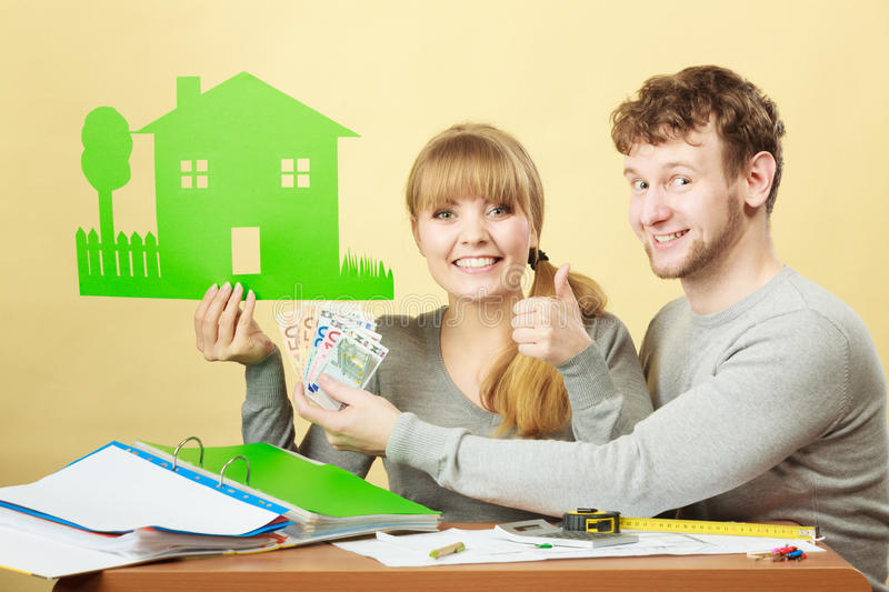 Couple with house and money. Home real estate credit mortgage concept. Couple with house and money. Young men and women counting banknotes and holding cartboard stock photo